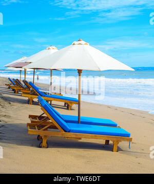 Deck chairs under parasols on sandy beach of tropical resort, Bali island, Indonesia - Stock Photo
