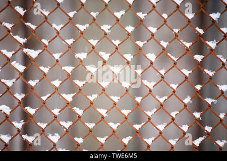 old metal fence grid pattern closeup with snow cover - Stock Photo