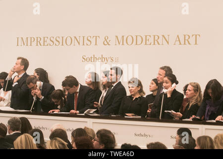 London, UK. 19th June 2019. Sotheby's staff and auctioneers take bids over the phone  at the Impressionist & Modern Art Evening Auction  at Sotheby's London which saw £99 Million $124million sales including Claude Monet's Nymphéas (1908)  which went under the hammer  for £23.7m- $29.8m and Modigliani's Portrait of an Anonymous Youth (1918) which sold  for £18.4m- $23.1m Credit: amer ghazzal/Alamy Live News - Stock Photo