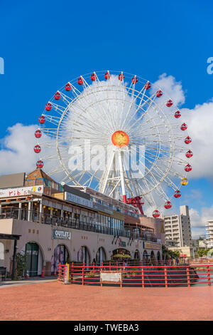 Mihama Carnival Park Ferris wheel located in the American Village neighborhood of Naha City decorated with palm trees near Sunset Beach in Okinawa. - Stock Photo