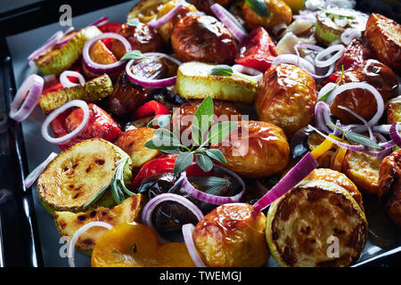 close-up of freshly roasted in an oven hot vegetables  - potatoes, eggplants, zucchini, tomatoes, bell peppers on a baking pan on a grey concrete tabl - Stock Photo