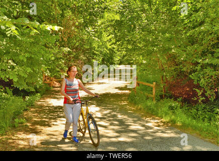 At a natural park, a woman takes her bike down the slope to avoid dangerous falls. You can enjoy the serene and bright atmosphere of the park. - Stock Photo