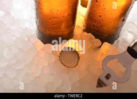 Beer glass bottles on ice with cap and bottle opener . Horizontal composition. Elevated view. - Stock Photo
