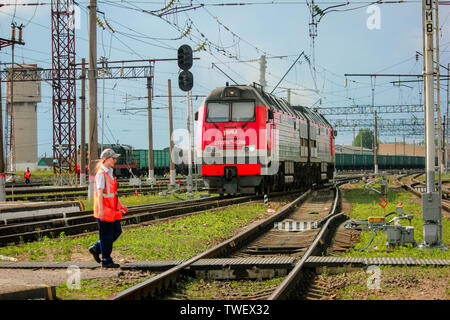 20.06.2019 Bryansk. Russia. Girl - employee of the railway station is on business through the rails. - Stock Photo