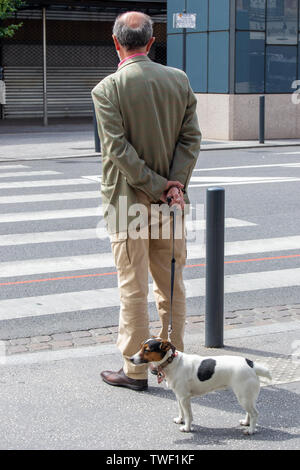 An old  man walking out his little dog on france streets - Stock Photo
