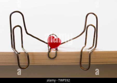 paper clips symbolizing a person sitting on a stack of white paper. family concept - Stock Photo
