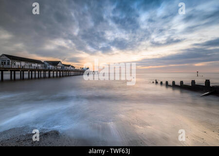 Southwold pier in Suffolk looking in between one of the sea defences on the sandy beach. - Stock Photo