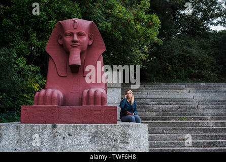 Woman using smartphone while sitting beside painted terracotta sphinx which is part of the grand terrace in Crystal Palace in London. - Stock Photo