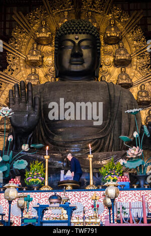Buddha statute at the Great Buddha hall by the Todai-ji Temple in Nara in Japan. - Stock Photo
