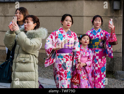 Tourists in western clothes and traditional dress taking photographs and using smartphones at the Chion-in Temple in Kyoto in Japan. - Stock Photo