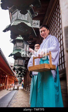 Low angle portrait of monks switching on lanterns at the Kasuga-taisha shrine in Nara in Japan. - Stock Photo