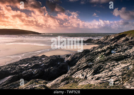 A spectacular sunset over Crantock Beach at low tide in Newquay in Cornwall. - Stock Photo