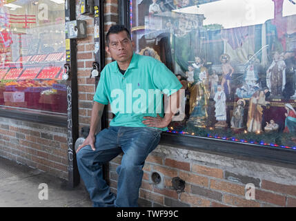 A man, likely to be South American, sits on a ledge lost in thought under the elevated subway on Roosevelt Avenue in Jackson Heights, Queens, New York - Stock Photo