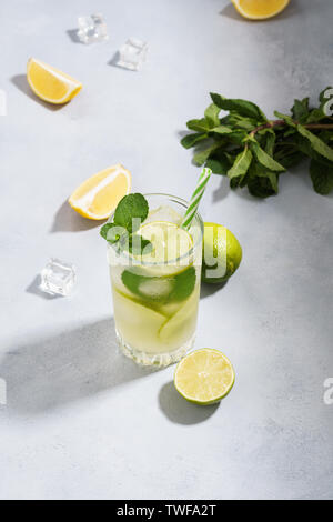 Cold lemonade with sliced lemon, lime and mint in a glass. Refreshing drink for summer. Shot with hard natural light. Copy space. - Stock Photo