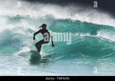 Spectacular surfing action as a surfer rides a wave in a jade coloured sea at Fistral in Newquay in Cornwall. - Stock Photo