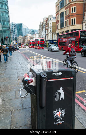 A Big Belly Solar litter bin overflowing with rubbish in a City of London street. - Stock Photo