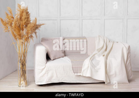 Scandinavian style livingroom with fabric sofa, pillows, plaid and  plant in vase on grey wall background - Stock Photo