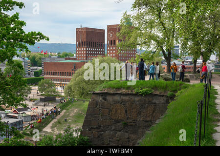 Oslo City Hall, view of people standing on the ramparts of the Akershus Festning (fortress) looking towards Oslo City Hall in the harbor area,  Norway - Stock Photo