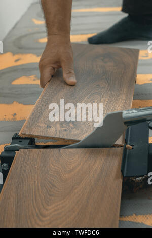 hand holding and cutting the laminate panel with a laminate cutter - Stock Photo