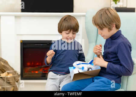Little brother receiving gift from older brother, on his birthday - Stock Photo