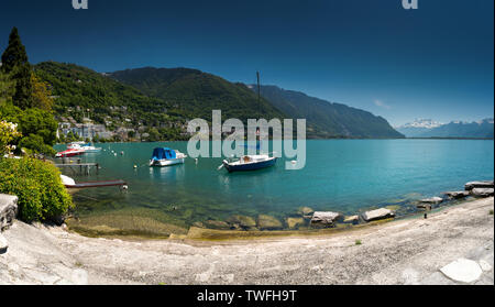 Montreux, VD / Switzerland - 31 May 2019: boats on the shores of Lake Geneva with great view of the Swiss Alps behind as seen from the Montreux Rivier - Stock Photo