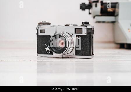 Old film camera on white plank background. Typewriter on the background. Vintage photo.