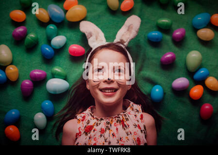 Overhead portrait of young girl wearing bunny ears surrounded by Easter eggs - Stock Photo