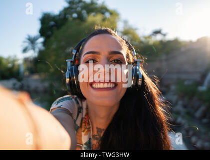 transgender model wearing sunglasses in the green park - Stock Photo