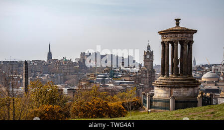 Elevated view of part of Edinburgh city centre featuring the Dugald Stewart monument, the Balmoral Hotel, Edinburgh Castle, New College, Scotland. - Stock Photo