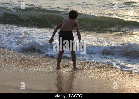 Young boy playing in the sea in Sri Lanka - Stock Photo
