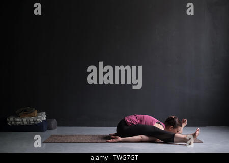 Young woman practicing yoga, doing Kurmasana, Tortoise posture, Turtle Pose - Stock Photo