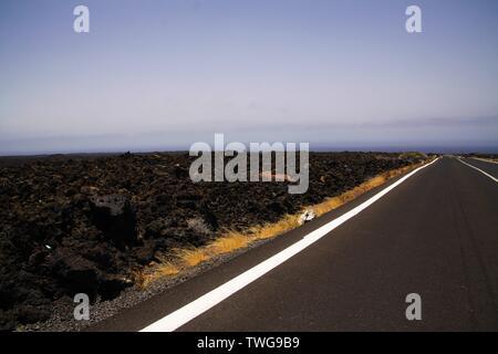 Lanzarote - Timanfaya NP: Driving trip on endless empty asphalt road between black lava rocks in barren landscape - Stock Photo