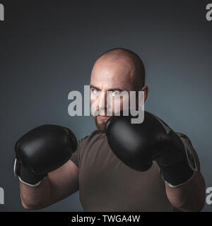 adult man with casual clothes and boxing gloves, looks directly at the camera. Concept of sport and determination in life. - Stock Photo