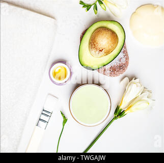 Beauty concept avocado skin care facial essence oil, soap, lily flower and towel on white background. - Stock Photo