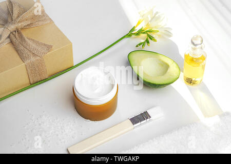 Beauty concept avocado, skin care facial essence oil, brush, lily flower and towel on white background. - Stock Photo