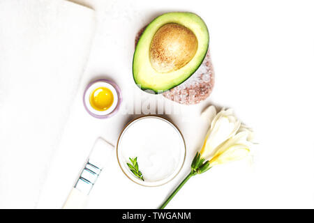 Avocado and jar of cream oil lily flowers and sea salt soap white towel on a white background. Facial treatment concept. Avocado skin care facial mask - Stock Photo