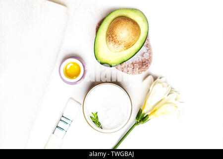 Avocado and jar of cream oil lily flowers and sea salt soap white towel on a white background. - Stock Photo