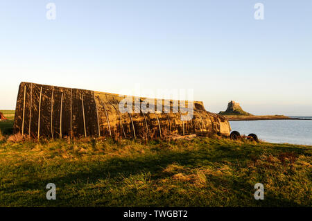 Old fishing boats turned upside down used as boat storage huts on the beach near to Lindesfarne Castle on Holy Island in Northumbelrand, Britain - Stock Photo