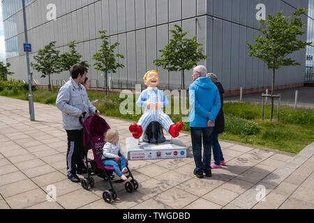 Glasgow, Scotland, UK. 20th June, 2019. Wee Wullie Winkie, created by David Graham. This sculpture is a refernce to the famous Scottish nursery rhyme Wee Willie Winkie written by Glasgwegian William Miller. It sees Oor Wullie dressed in his nightcap and pyjamas, sitting on his bucket, which depicts the Glasgow skyline at night. He is stretching his legs after waking from a  long night's sleep. The sculpture is part of Oor Wullie's BIG Bucket Trail. Credit: Skully/Alamy Live News - Stock Photo