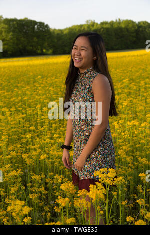 A beautiful teenage girl laughs while in a field of yellow in Fort Wayne, Indiana, USA. - Stock Photo