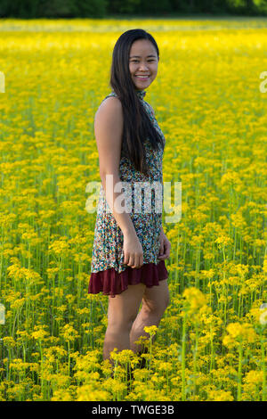 A beautiful teenage girl looks toward the camera and smiles while standing in a field of yellow in Fort Wayne, Indiana, USA. - Stock Photo