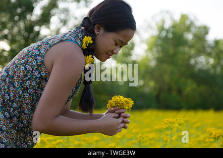 A beautiful teenage girl with flowers in her hair makes a bouquet in Fort Wayne, Indiana, USA. - Stock Photo
