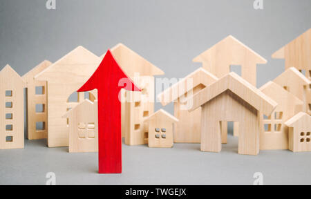 Red arrow up and miniature wooden houses. The concept of rising property prices. High mortgage rates. Expensive rental apartment. Growing demand for h - Stock Photo