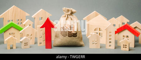 Red arrow up, money bag and miniature wooden houses. The concept of rising property prices. High mortgage rates. Expensive rental apartment. Growing d - Stock Photo