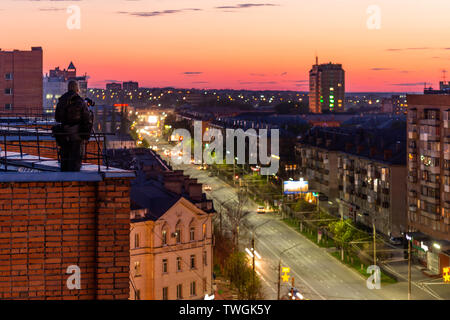 photographer shooting night sity from edge of red brick condominium roof somewhere in eastern europe - Stock Photo