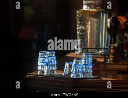 interior bar at the Grafton pub, kentish town, glasses and water dispenser lit by sunshine, - Stock Photo