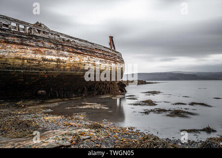Abandoned old fishing boats rotting on the shore of the Sound of Mull at Salen on the Isle of Mull - Stock Photo