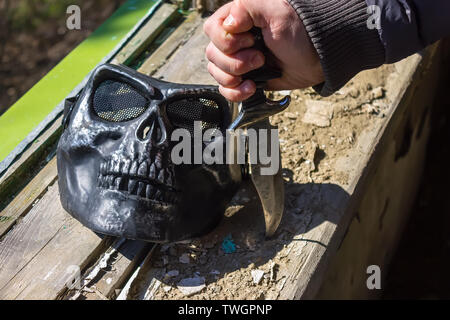 Knife in hand and mask near the destroyed window - Stock Photo