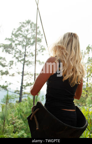 Rear view of young blonde female sitting in a swing with a view of the woods. San José del Pacífico, Mexico. May 2019 - Stock Photo