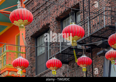 Red-and-gold Chinese lanterns in front of an old brick building in San Francisco, California, USA.